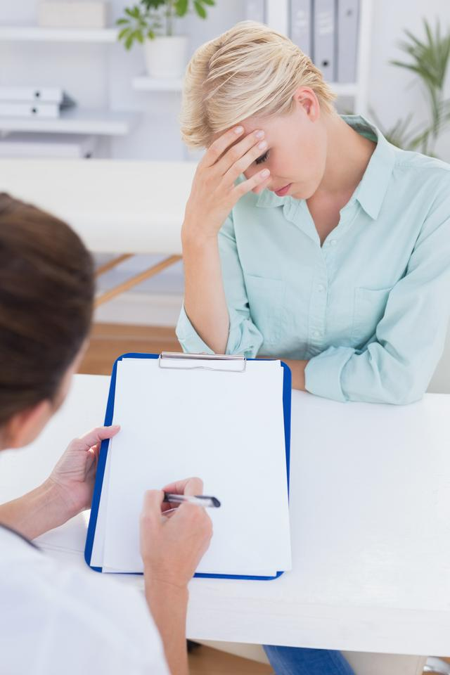 """""""Patient with head ache ache speaking with her doctor"""" stock image"""