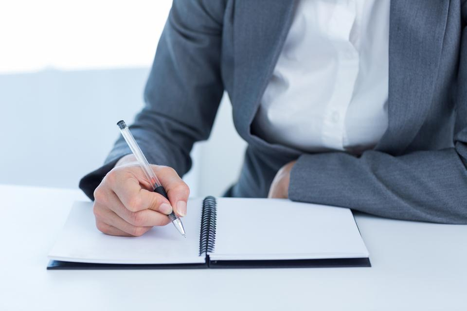 """Businesswoman writing in her diary"" stock image"