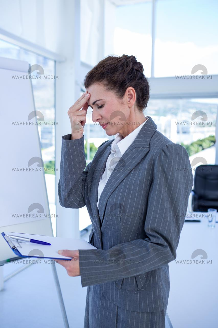 """""""Irritated businesswoman looking at clipboard"""" stock image"""