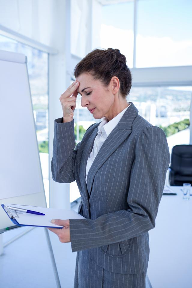 """Irritated businesswoman looking at clipboard"" stock image"