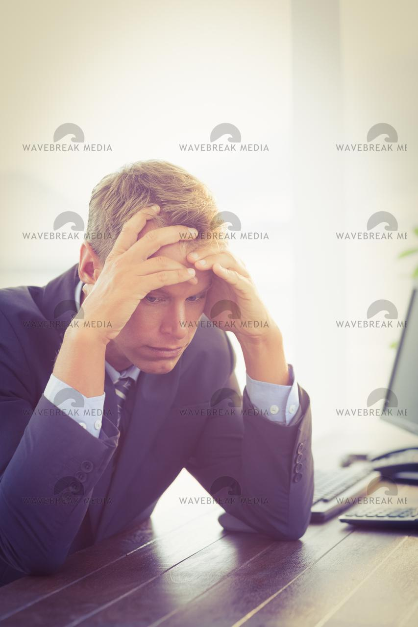"""Irritated businessman looking his desk"" stock image"