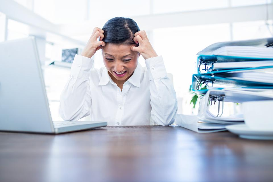 """Businesswoman getting stressed at her desk"" stock image"