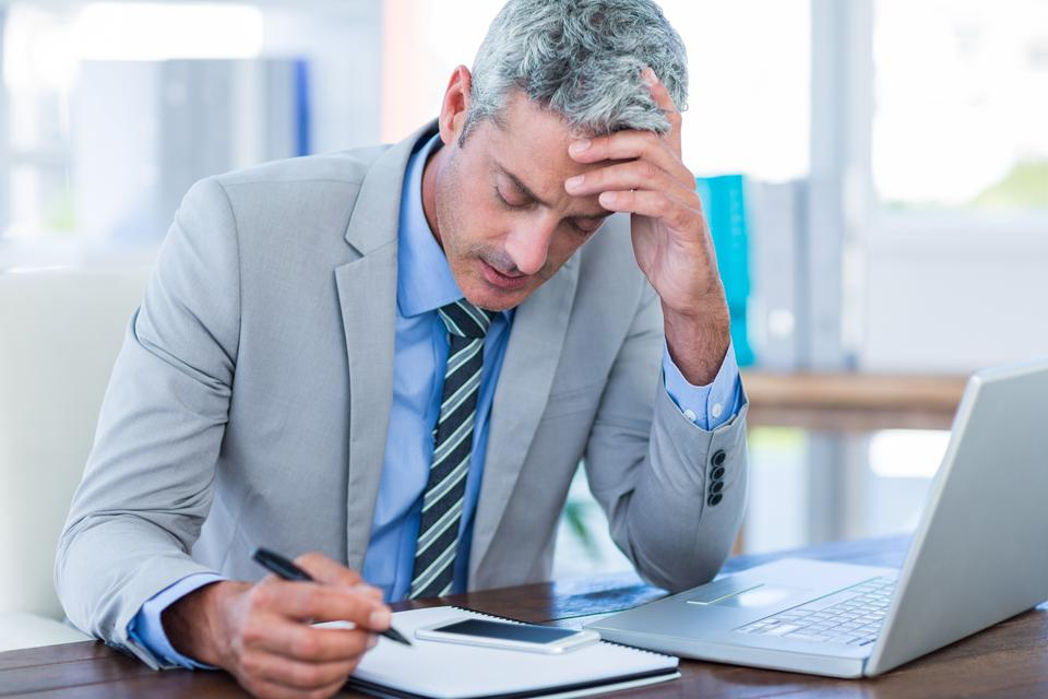 """Irritated businessman trying to work"" stock image"