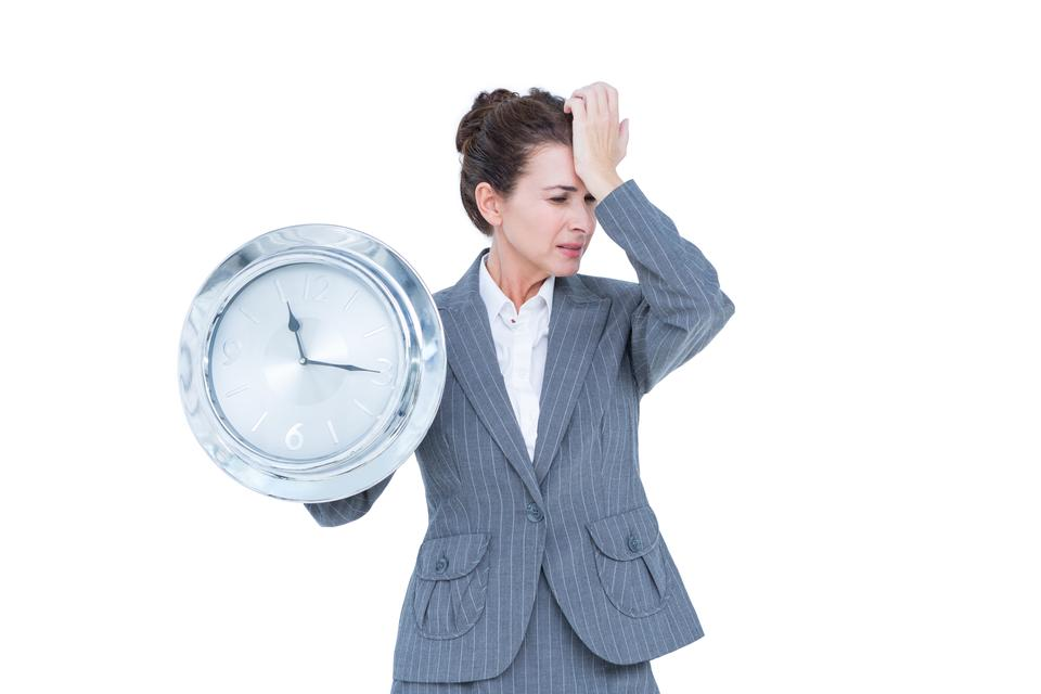 """Businesswoman in suit holding a clock"" stock image"