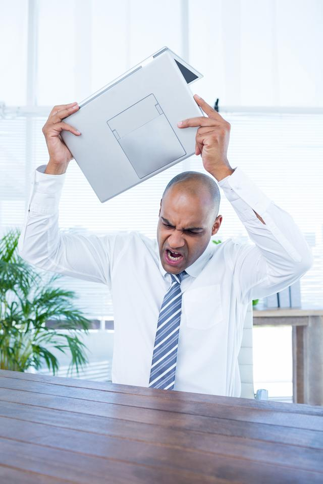 """Irritated businessman about to break his laptop"" stock image"