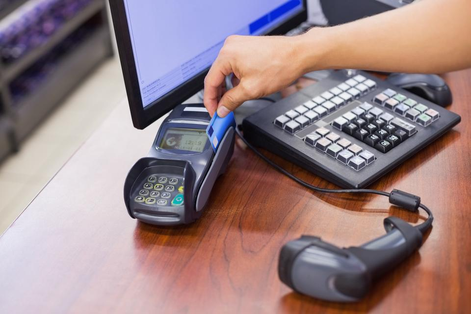 """""""Staff scan a credit card for paying products"""" stock image"""