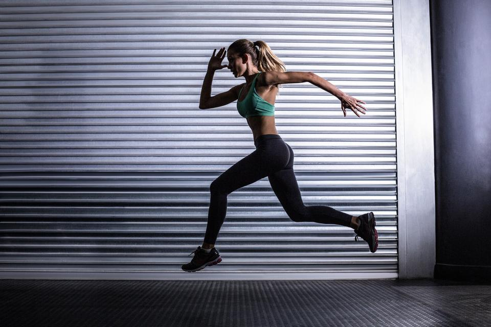 """Muscular woman running in exercise room"" stock image"