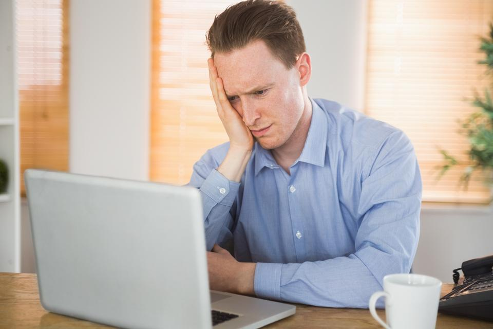 """Fearful businessman looking at his laptop"" stock image"