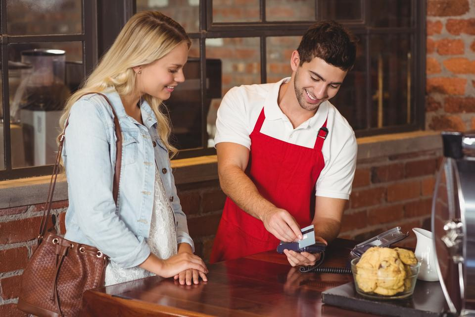 """""""Smiling waiter swiping the credit card"""" stock image"""