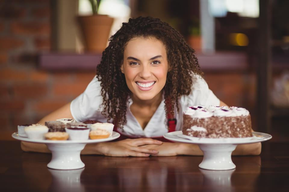 """Waitress bending over chocolate cake and cupcakes"" stock image"