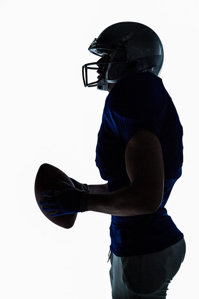 """""""Side view of sportsman holding football"""" stock image"""