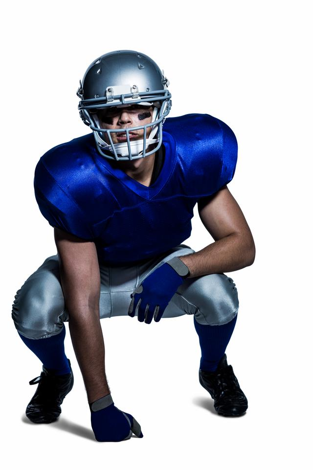 """""""American football player in uniform crouching"""" stock image"""