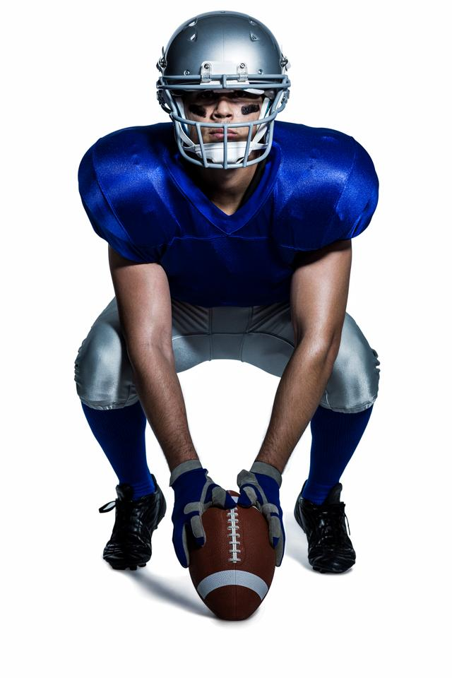 """""""American football player with ball crouching"""" stock image"""