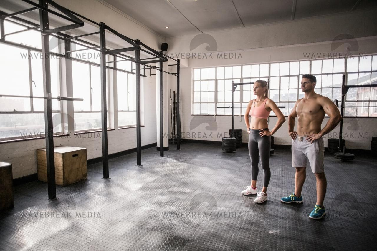 """""""Crossfit couple posing with hands on hips"""" stock image"""