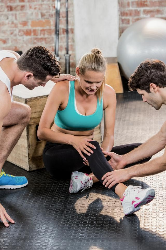 """Men helping an injured woman at gym"" stock image"