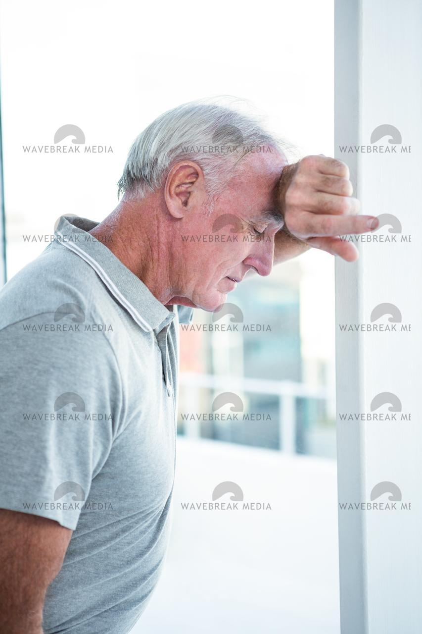 """Depressed mature man leaning on wall"" stock image"