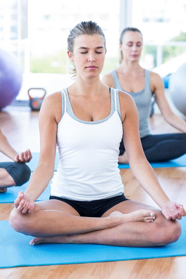 """Fit women doing lotus pose"" stock image"