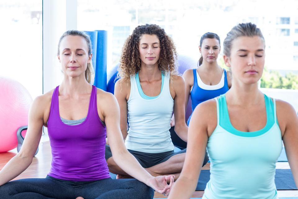 """Cropped image of women doing easy pose in fitness center"" stock image"