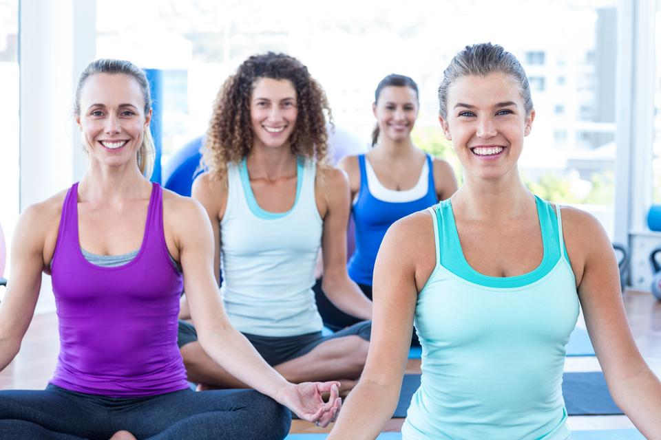 """Women smiling while doing easy pose in fitness studio"" stock image"