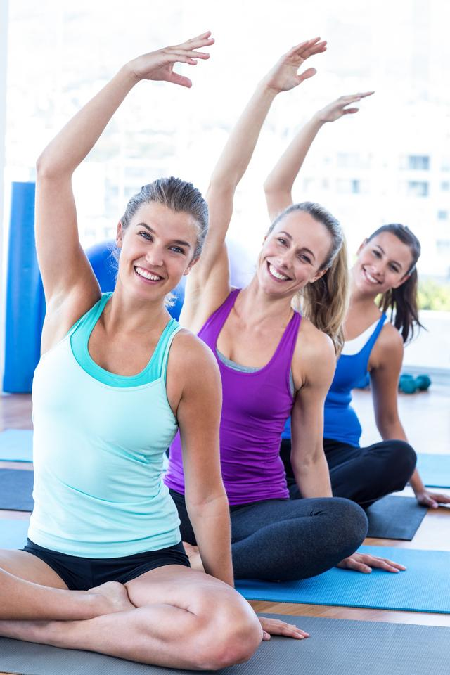 """Portrait of happy women in easy pose with hands raised"" stock image"