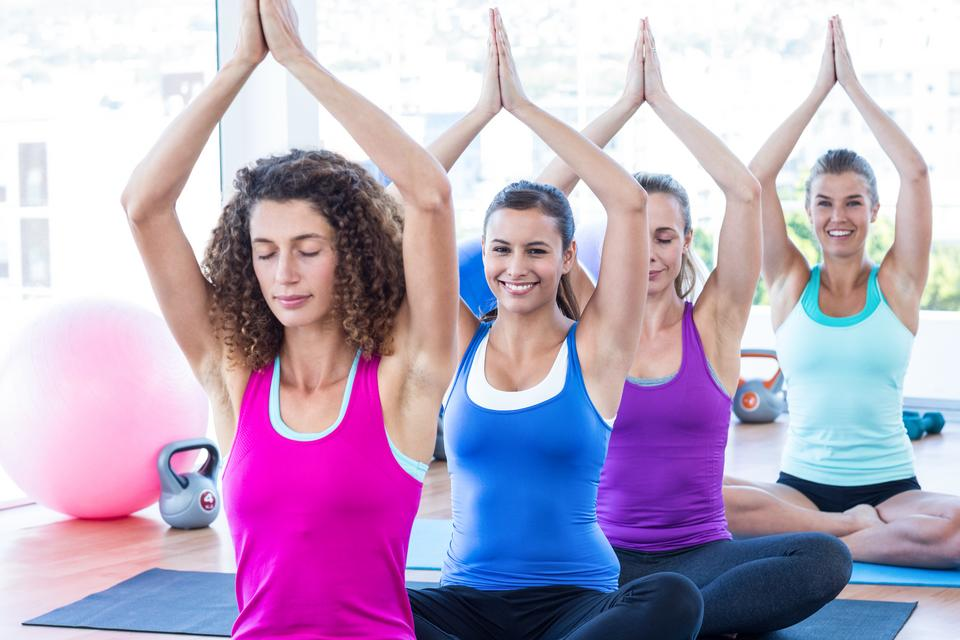 """Women sitting in fitness studio with hands joined overhead"" stock image"