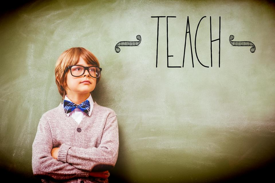 """""""Teach against boy with arms crossed looking up at blackboard"""" stock image"""