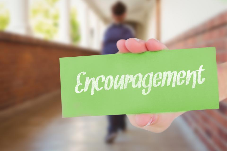 """""""Encouragement against pretty teacher helping pupils in classroom"""" stock image"""