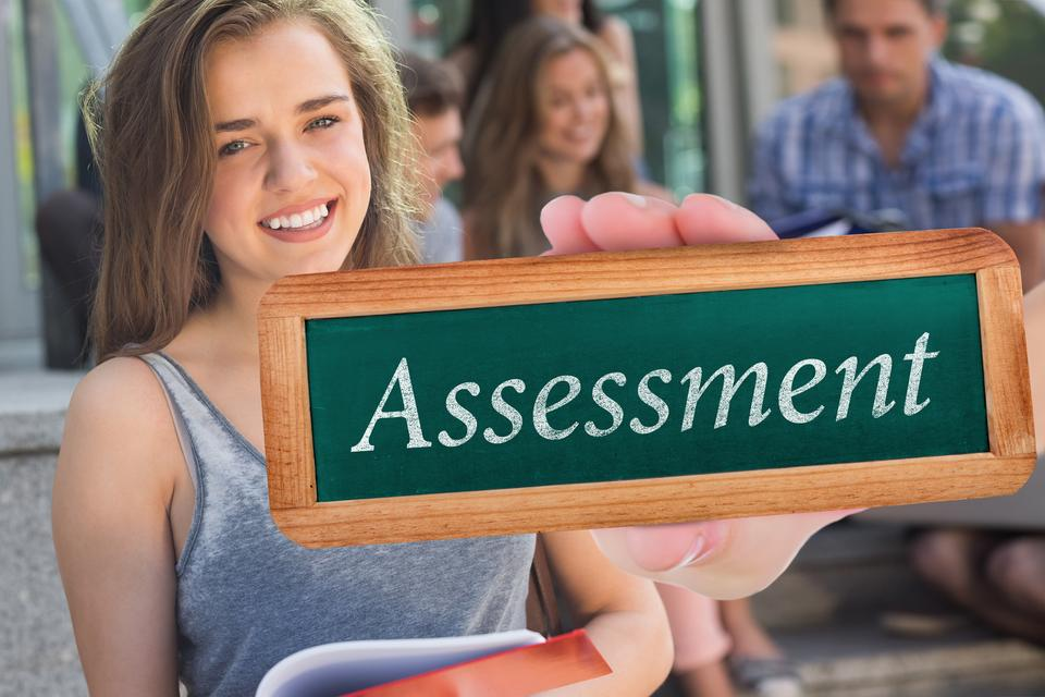 """Assessment against pretty student smiling at camera outside"" stock image"