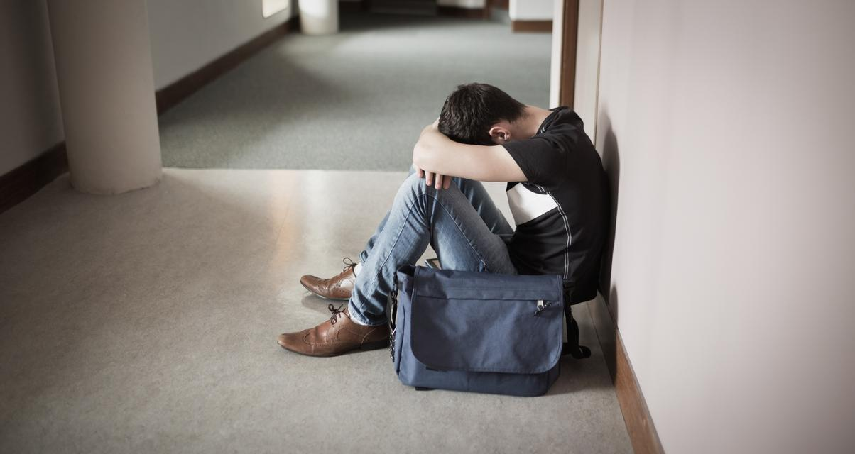 """Depressed male student with head on knees"" stock image"