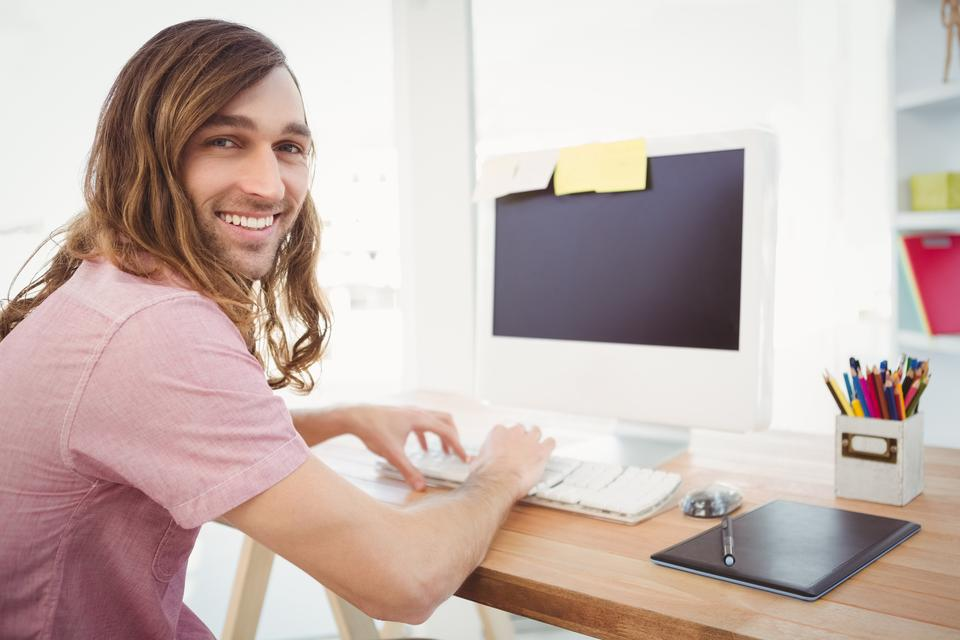 """""""Portrait of happy hipster typing on keyboard in office"""" stock image"""