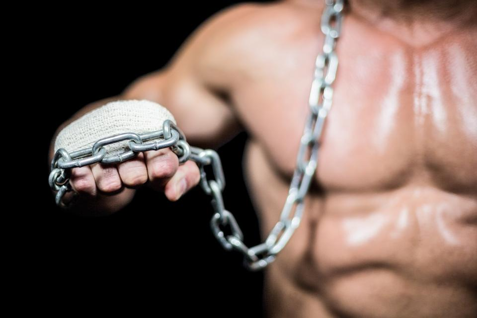 """""""Midsection of bodybuilder fist with chain"""" stock image"""