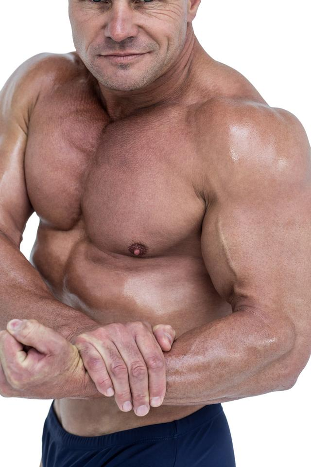"""""""Midsection of smiling bodybuilder flexing muscles"""" stock image"""