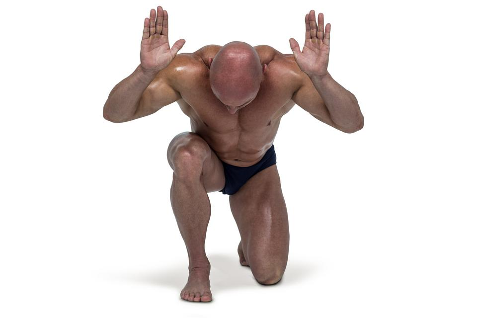 """""""Muscular man bending on knee with arms raised"""" stock image"""