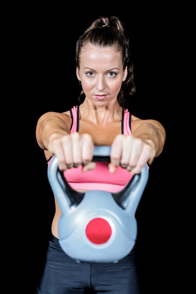 """Portrait of fit woman lifting kettlebell"" stock image"