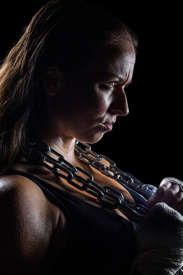 """Side view of female angry athlete holding chain"" stock image"