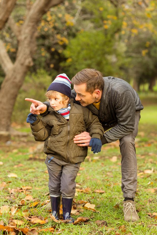 """Young father showing something to his cute son"" stock image"