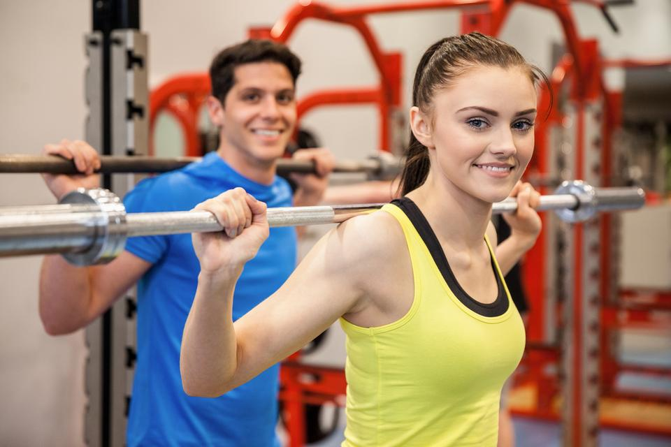 """Man and woman lifting barbells together"" stock image"