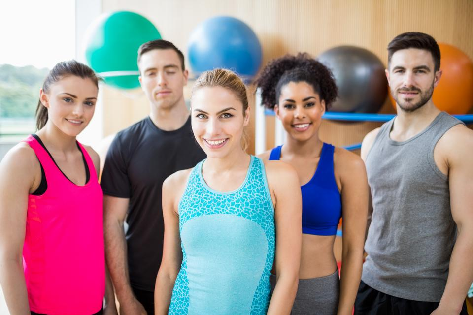 """""""Fitness class smiling at camera in studio"""" stock image"""