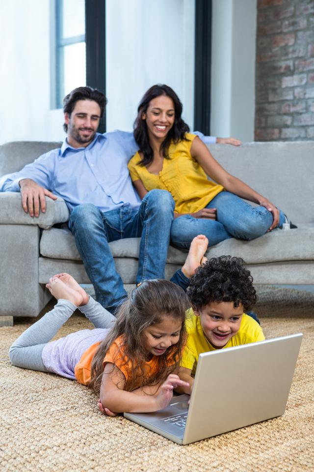 """""""Children laying on carpet in living room using laptop"""" stock image"""