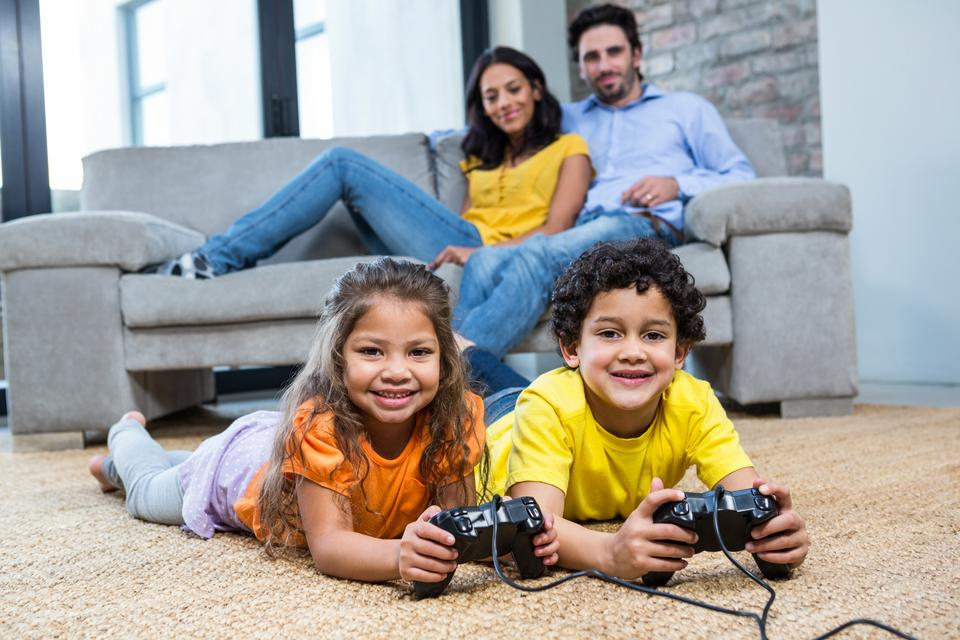 """""""Children playing video games on the carpet in living room"""" stock image"""