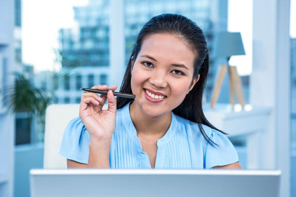 """""""Smiling young businesswoman sitting at her desk"""" stock image"""