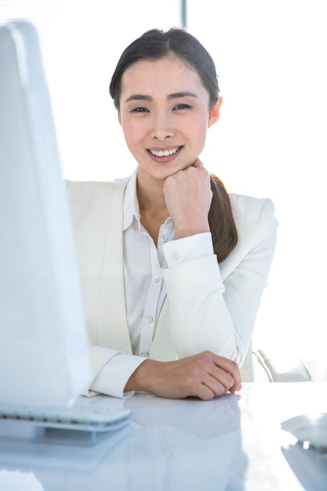 """""""Smiling businesswoman working at her desk"""" stock image"""