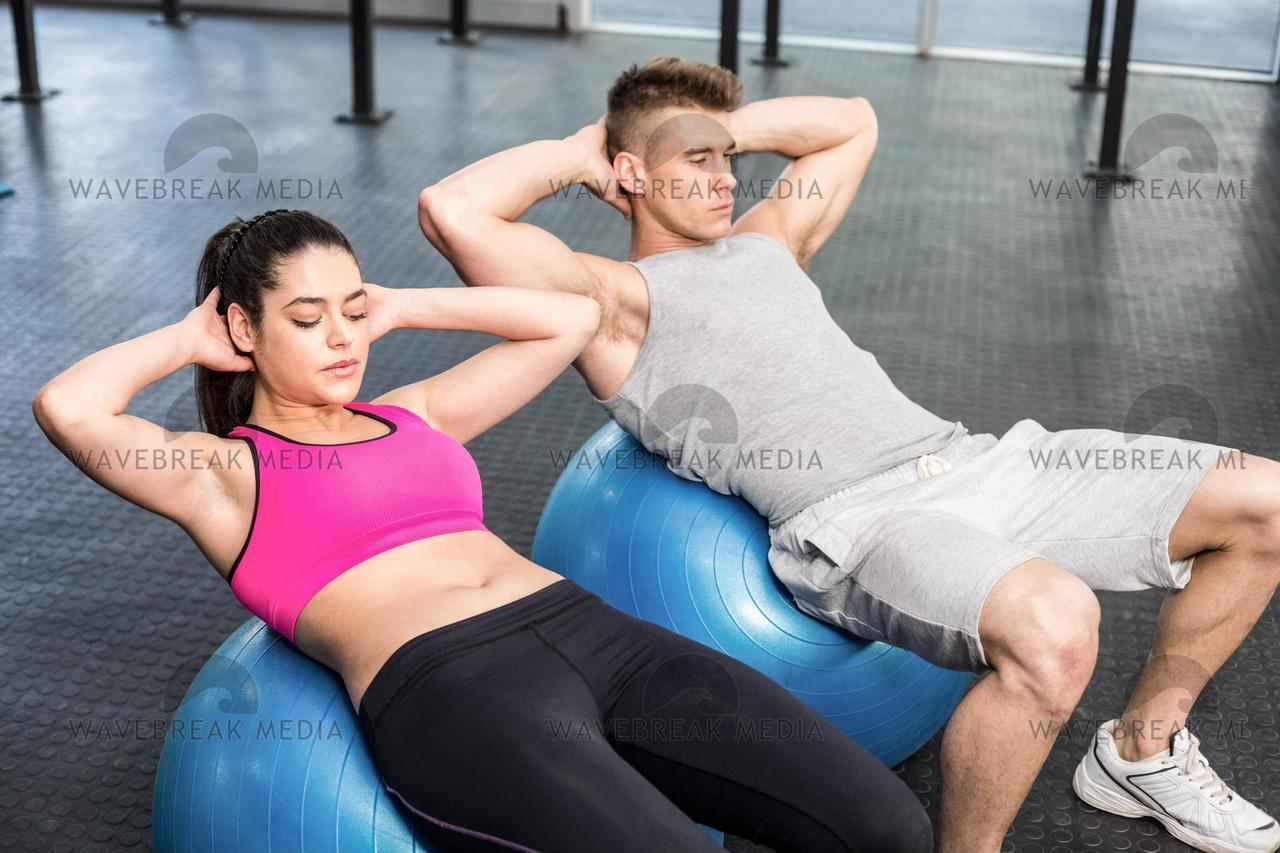 """Fit couple doing abdominal crunches on fitness ball"" stock image"