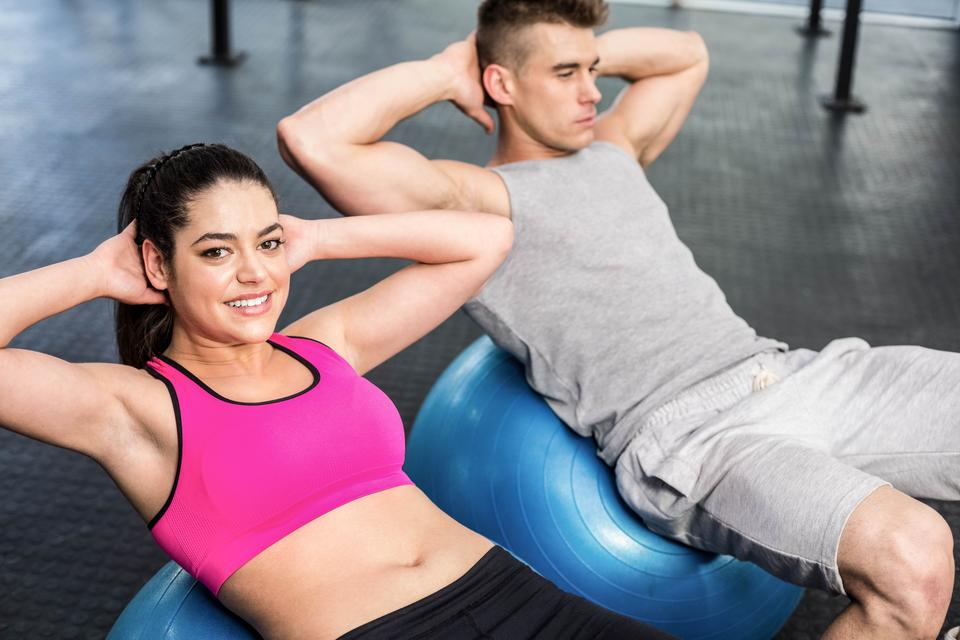 """""""Fit couple doing abdominal crunches on fitness ball"""" stock image"""
