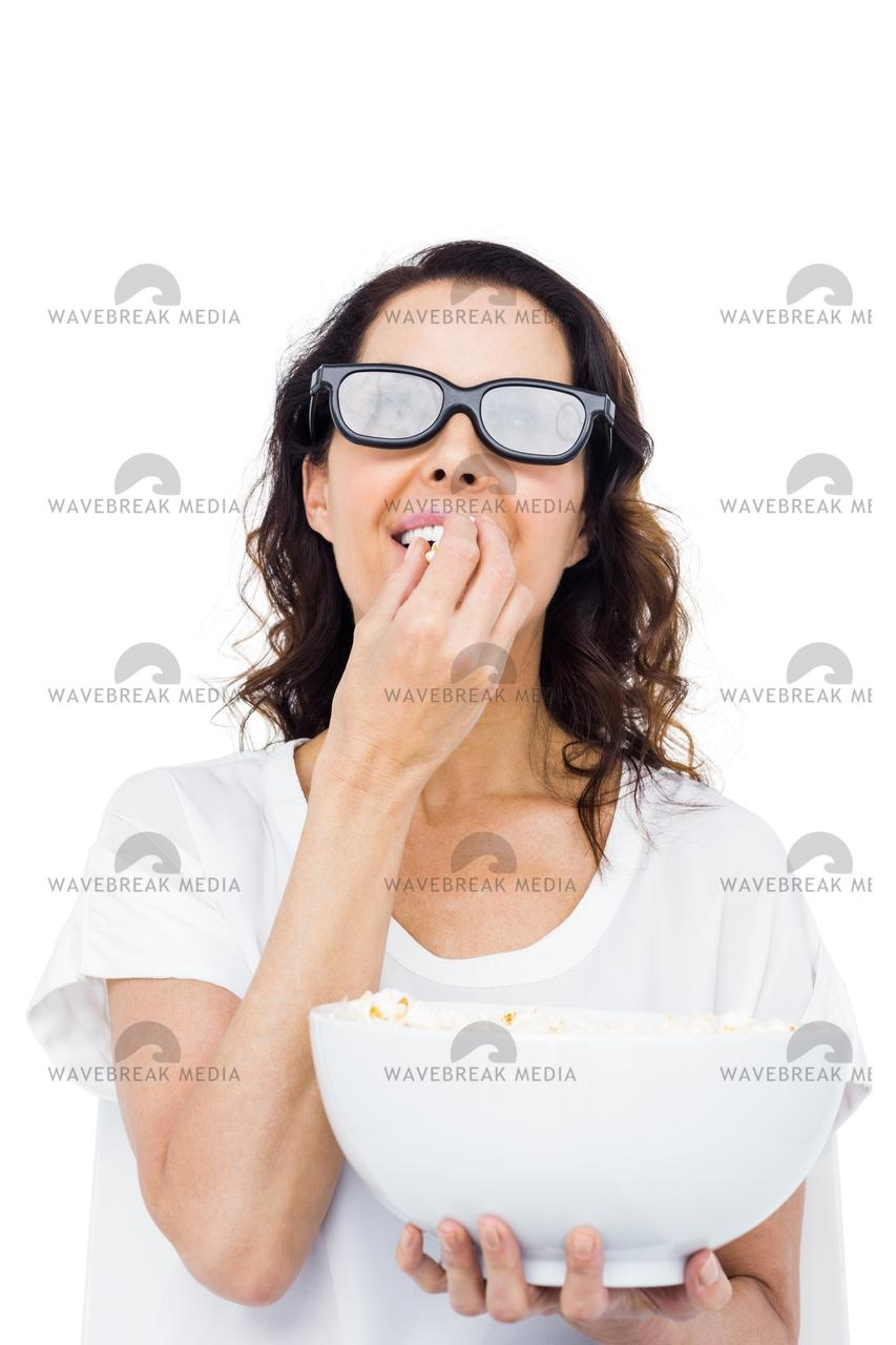 Pretty woman with 3D glasses eating popcorn - License, download or