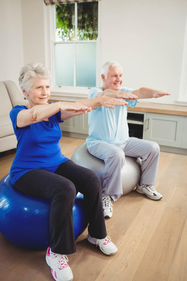 """Senior couple exercising on exercise ball"" stock image"