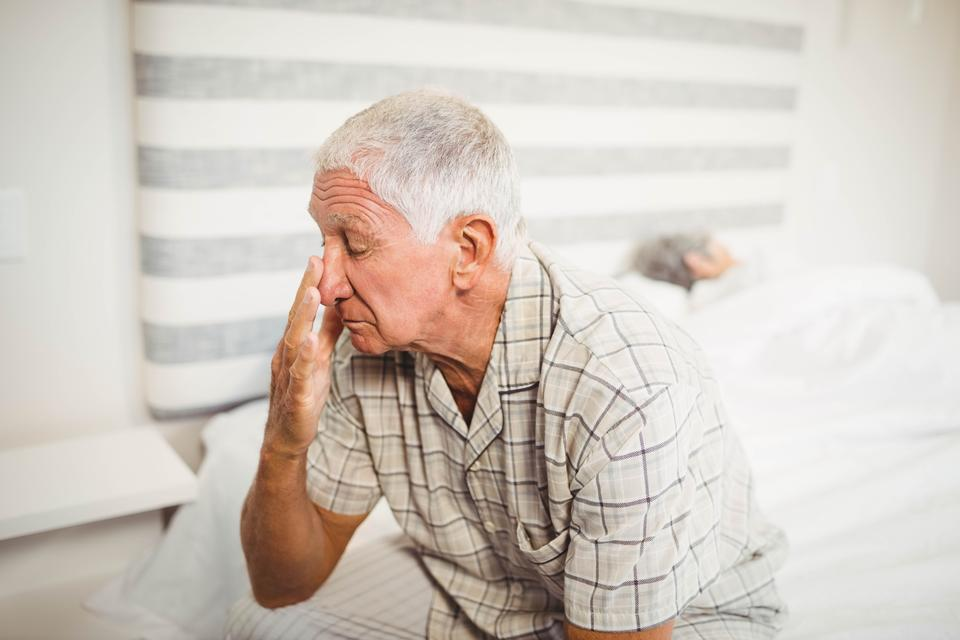 """Senior man sitting on bed"" stock image"