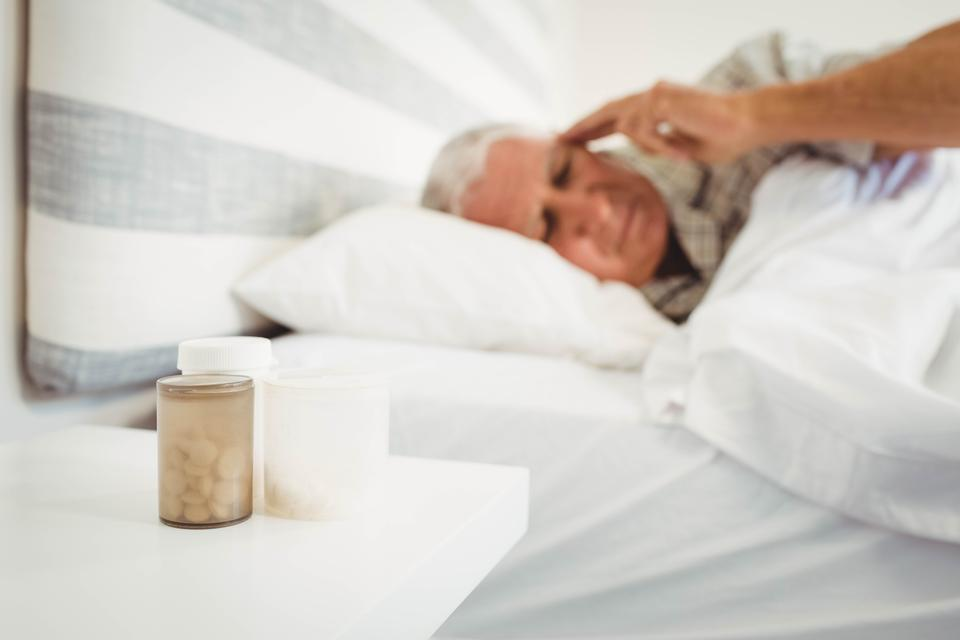 """Pillboxes on a side table near bed"" stock image"