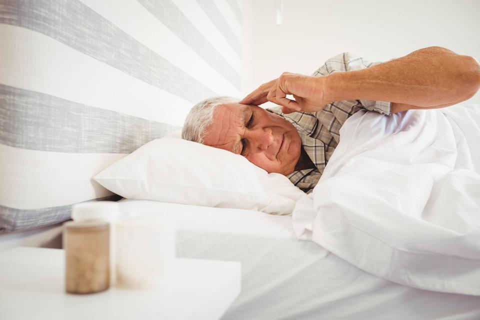 """Frustrated senior man lying in bed"" stock image"