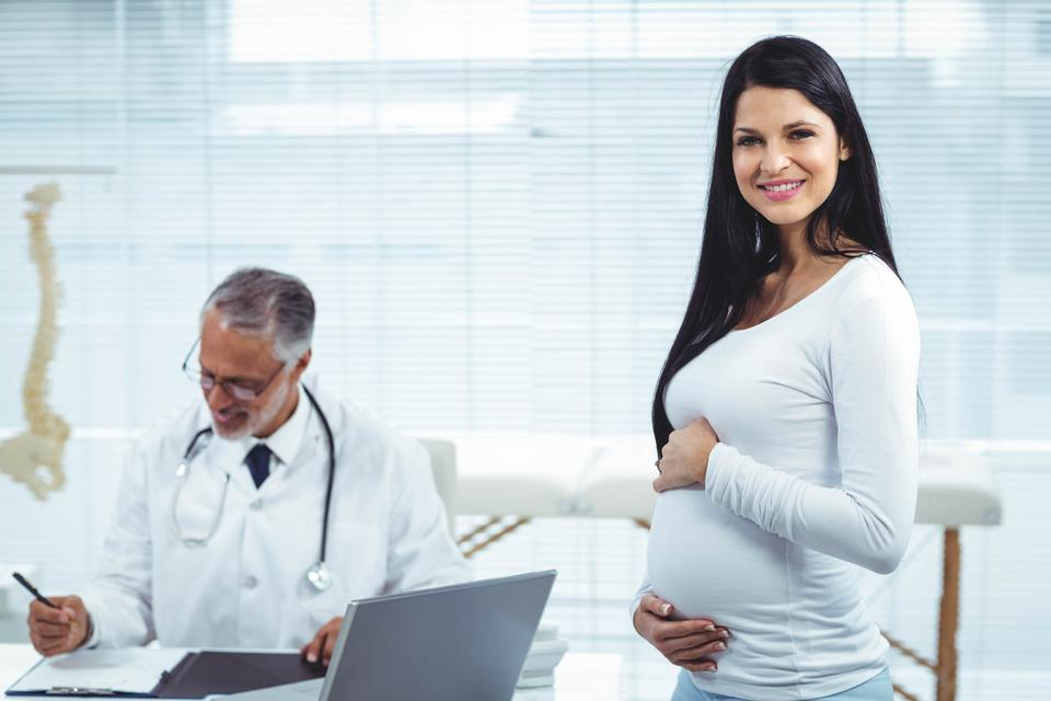 """""""Pregnant woman with doctor at clinic"""" stock image"""